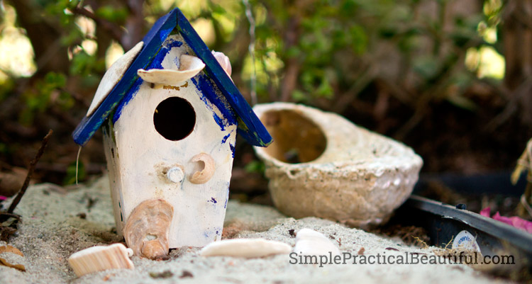 A blue and white beach house is perfect in a setting with shells for a beach fairy.