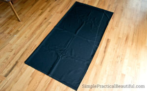 How to make a cloak: fold fabric into fourth, curve the bottom, cut a neck, and slope the sides.