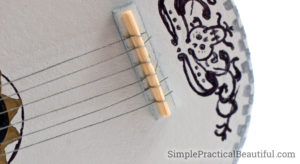 Threading the strings of the Coco guitar