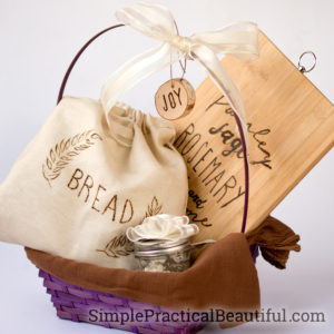 Fresh bread gift basket, including a bread bag, a decorated cutting board, homemade bread, and whipped butter