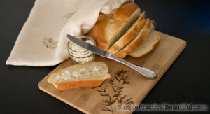 Fresh bread gift idea, including a bread bag, a decorated cutting board, homemade bread, and whipped butter