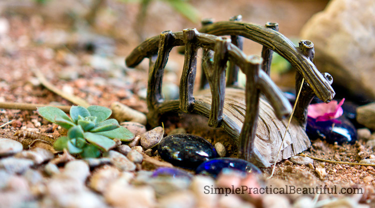 A fairy bridge passes over a stream made from blue glass stones.