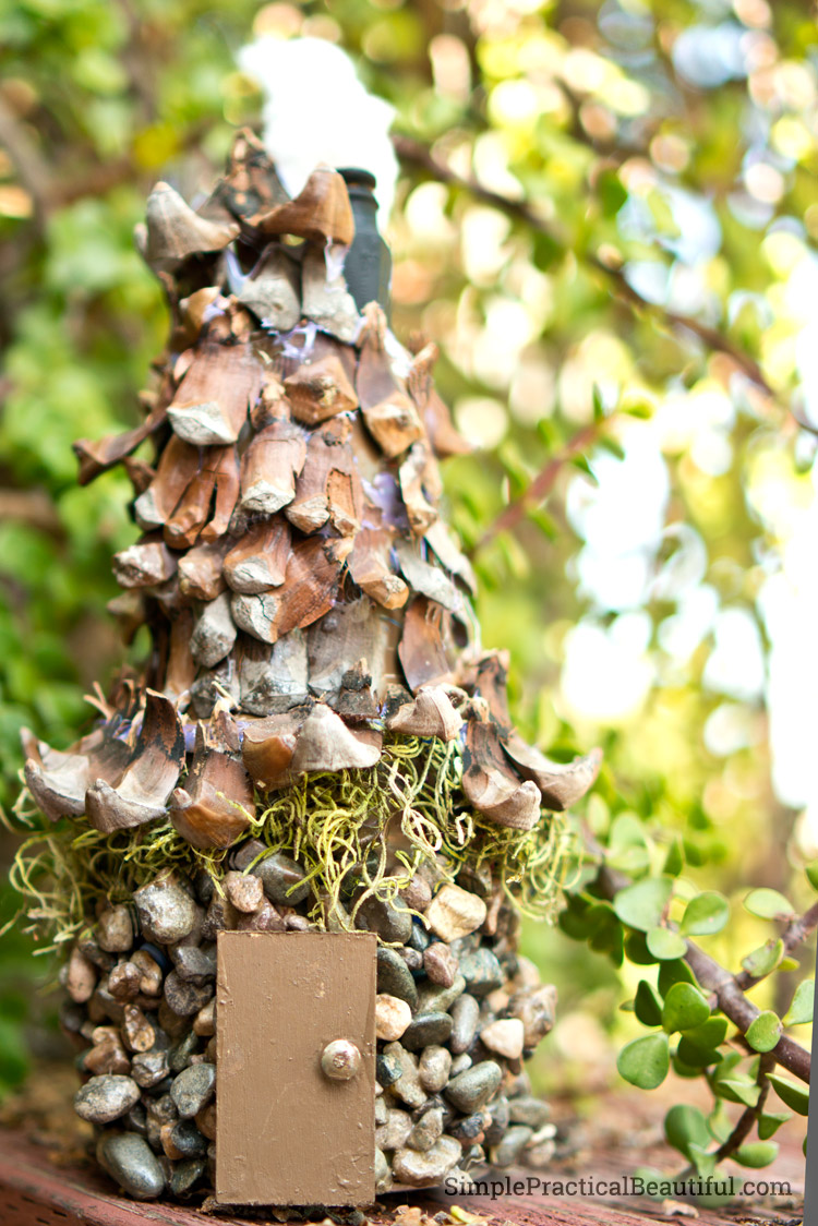 A fairy house made with gravel and pinecone shingles.
