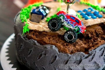 A monster truck birthday party cake made to look like a tire cake with a monster truck track