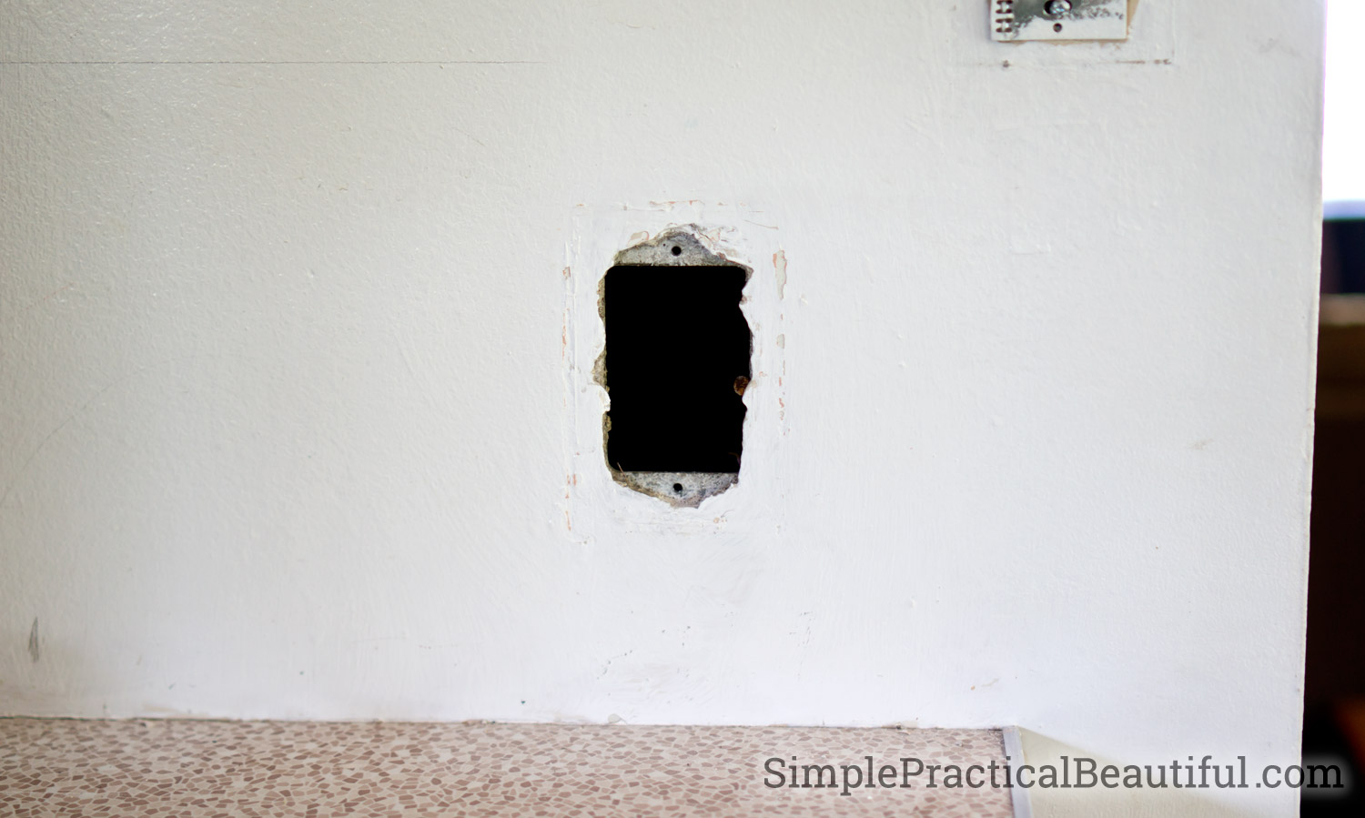 A hole in the wall that needs to be repaired from an empty phone outlet