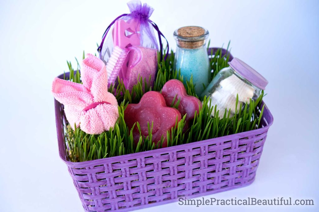 A spa gift basket filled with living grass and DIY soaps, bath salts, bath bombs, a pedicure kit, and a washcloth bunny