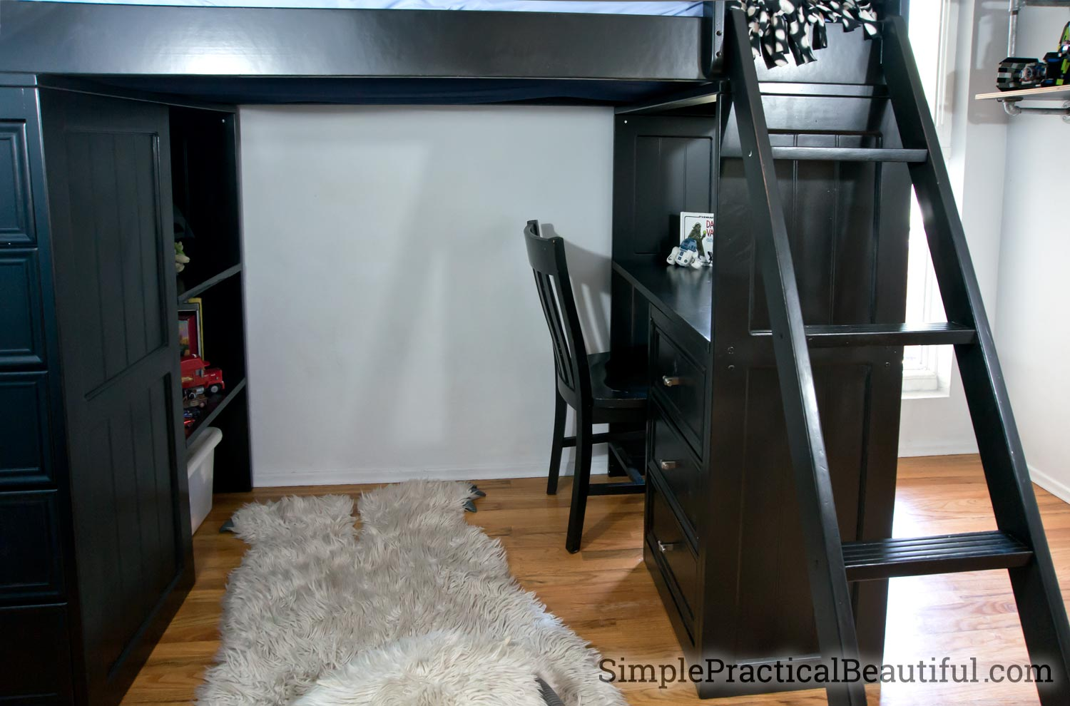 A loft bed with a desk area refinished in black with extra lighting added