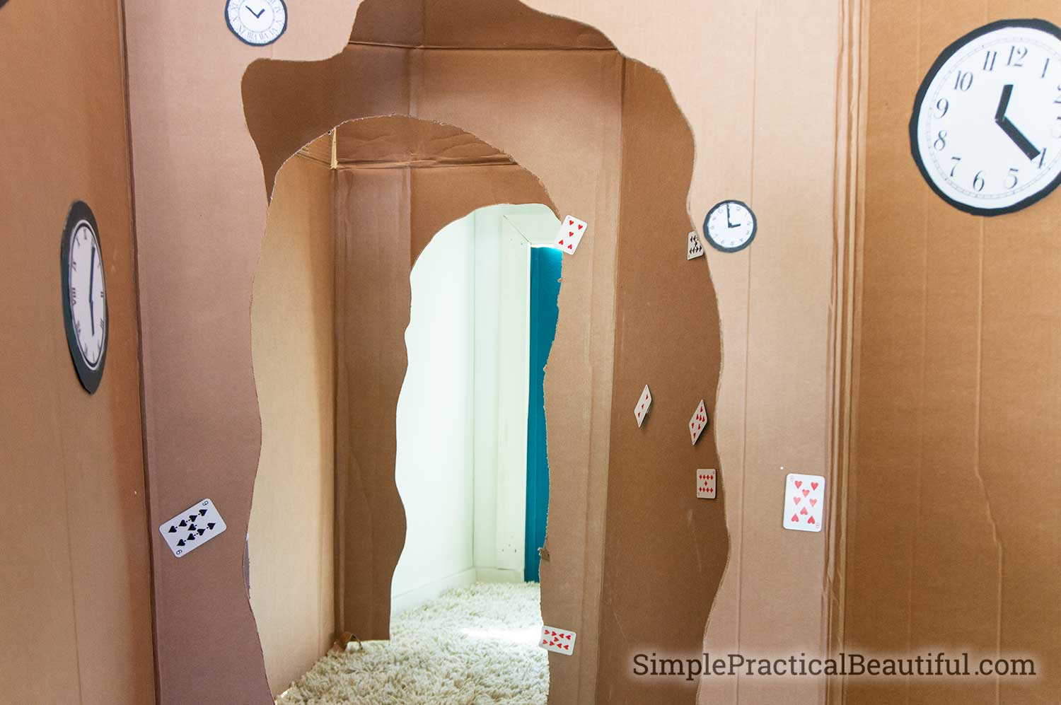 A cardboard rabbit hole that leads to the entrance of an Alice in Wonderland party and a Mad Hatter's Tea party