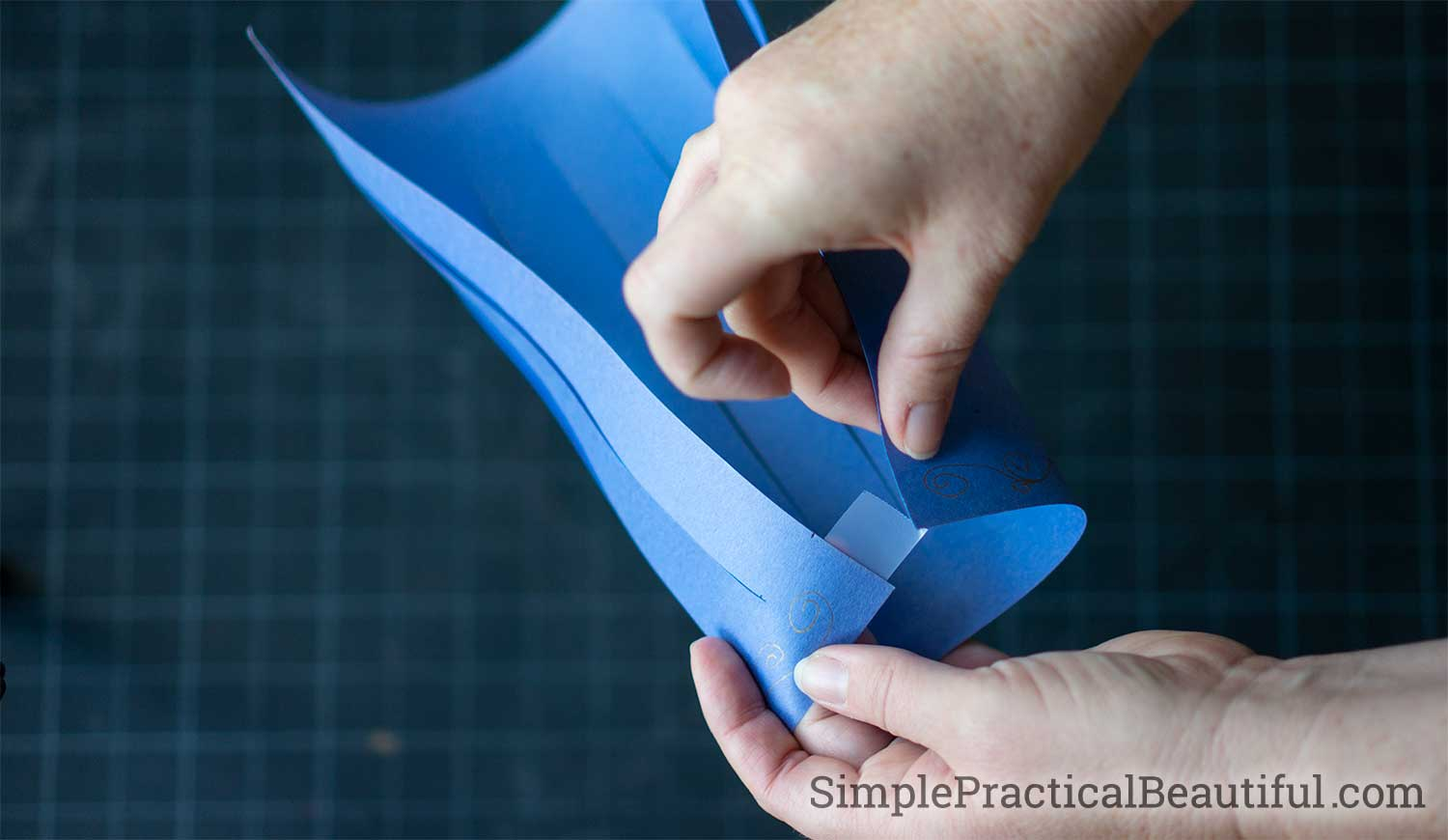 Tape the sides of the paper lantern together at the top and bottom