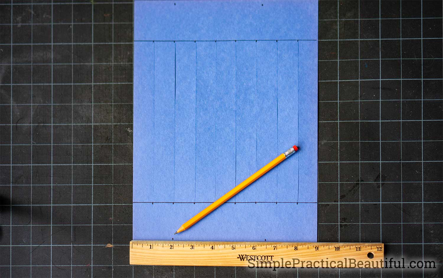 Measure and mark the construction paper accurately to make a lantern that doesn't end up lopsided