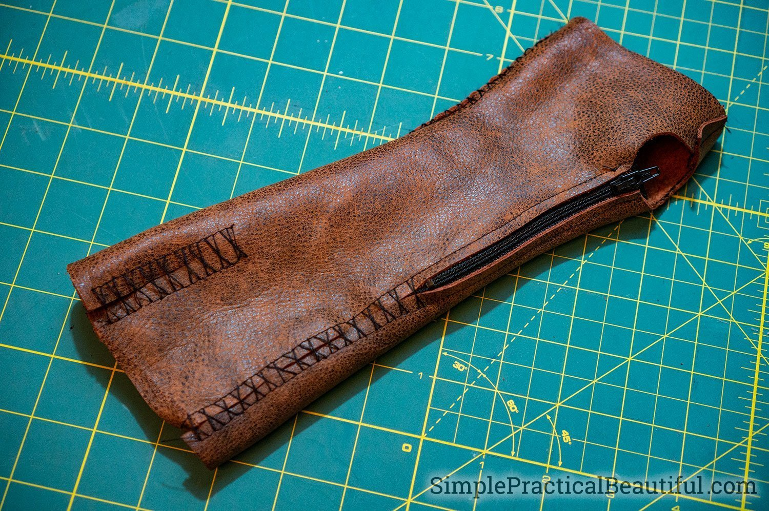 Make fingerless leather gloves by hand sewing the leather pieces together