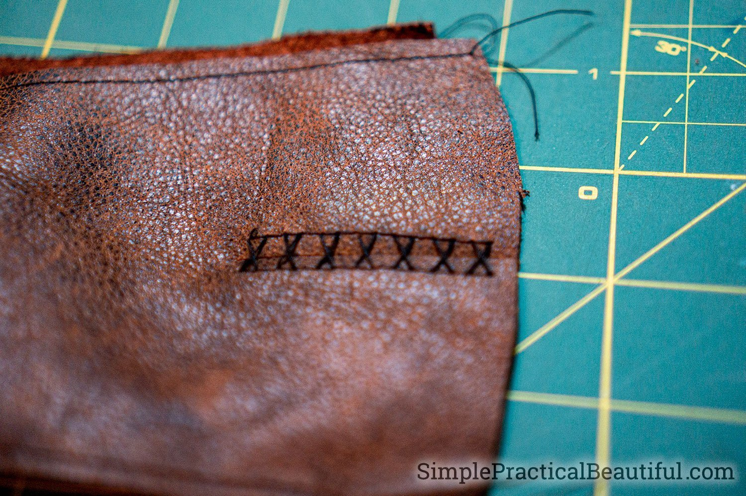 Sew the leather gloves together by hand using the holes from the machine stitch