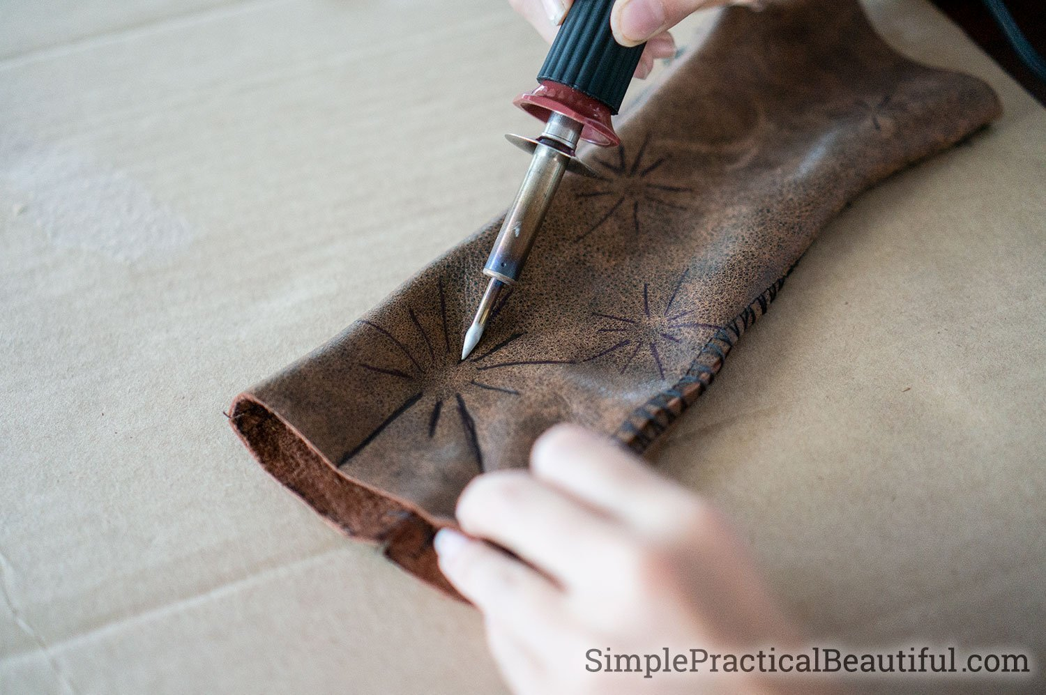 Burn a pattern in leather gloves with a wood burning tool